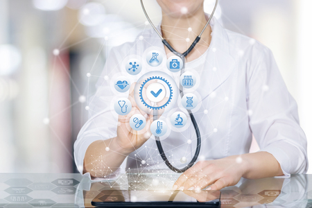A closeup of doctor sitting at a glass table and touching a circle of medical icons with quality sign in the middle with her stethoscope at the blurred hospital room background.