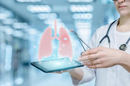 Un médecin met une pièce de puzzle manquante au moyen d'une pince médicale dans un modèle de poumon numérique suspendu au-dessus d'une tablette dans sa main. L'approche innovante dans le traitement des maladies dangereuses.