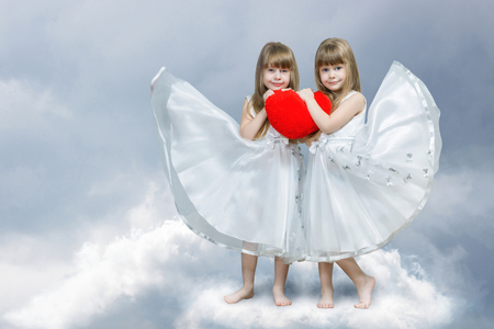 Two smiling cute blondie sisters twins in white dresses are holding a big bright red heart together standing barefoot on the cloud at light blurred background. The concept of tight family relations. Imagens