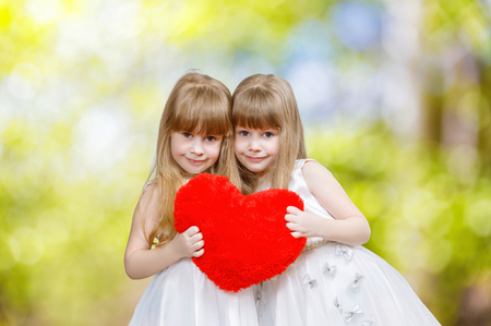 A closeup of two smiling cute blondie sisters twins in white dresses holding a big bright red heart at light blurred background. The concept of tight family relations.