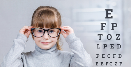 A smiling child in glasses is standing with checking table with letters behind her at the blurred medical room background. The concept of ophthalmologic diagnostic, treatment and correction.