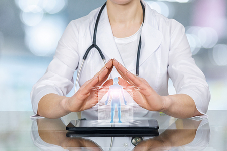 Young doctor is sitting at a table holding her hands in protective gesture above a human figure model. The total medicine, life and health insurance concept. Archivio Fotografico