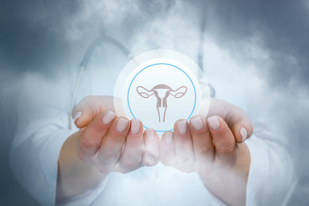 A closeup of a doctor holding a sphere with uterus image inside at the blurred background.