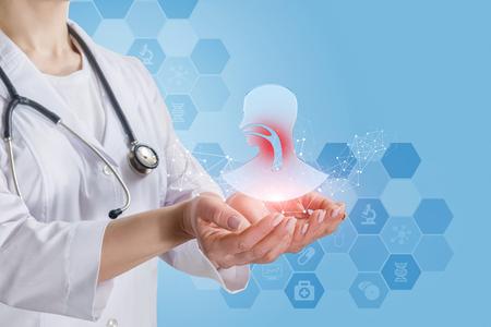 Un primer plano de un joven médico con un estetoscopio sosteniendo un modelo de cabeza humana con inflamación de la garganta con un sistema de servicio médico de peine en primer plano. El concepto de otorrinolaringología como unidad médica independiente.