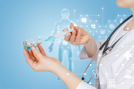 A closeup of a doctor operating with a vaccination syringe with substance and a bottle with digital human figure model behind and total medical service structure at the forehand. Stock fotó