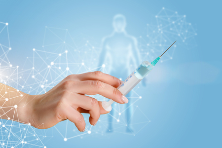 A female hand holding a vaccination syringe with substance within wireless connections and with the human figure model behind at light background. The compulsory vaccination and treatment concept.