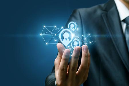 Un primer plano de la mano de un empresario sosteniendo una estructura de conexiones inalámbricas y modelos de imágenes de figuras humanas en un fondo oscuro. El concepto de clientes potenciales. Foto de archivo