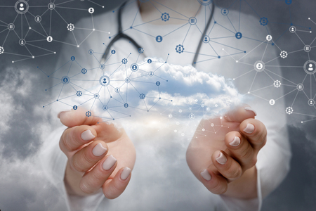A closeup of doctor holding information and data cloud surrounded with network social net of connections and human figures model images. Online medical consultation, information and data concept.