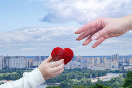 A closeup of a small child hand giving a bright red knitted heart to a female adult hand at the big city panorama background. Charity, donation and family relations concept. Standard-Bild - 121171600
