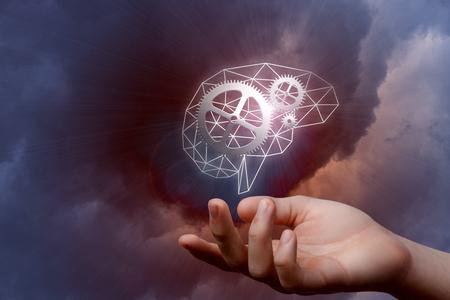 Eine Nahaufnahme eines digitalen Gehirnmodells mit Getriebefunktionsmechanismus nach innen hängend über einer Hand am dunklen Hintergrund. Das Konzept der menschlichen Intelligenz und des innovativen Denkens.