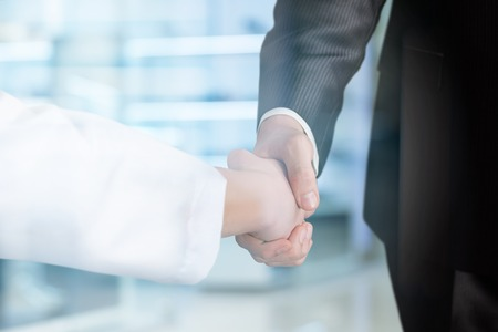A closeup of a doctor and businessman shaking hands at the hospital interior background. The medicine governmental and public support concept.