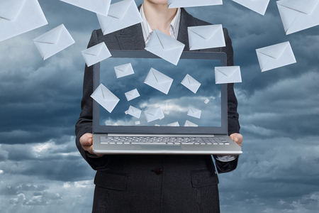 A businesswoman is holding a notebook with envelope icons flying from it at the grey background. The social networks concept. Stock Photo