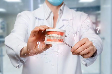 A closeup of a doctor holding a denture model surrounded with wireless connections and question marks and pointing at teeth with some medical tool. The concept of proper diagnostics and treatment. Stok Fotoğraf - 120976865