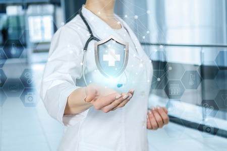 A young doctor is holding a shield with medical symbol inside at the blurred hospital hall background. The health insurance concept.