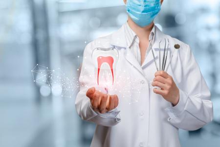 Un gros plan du dentiste tenant l'image d'un modèle de dent numérique avec des racines et un ensemble d'outils de médecine dentaire à l'arrière-plan flou de la chambre d'hôpital. Le concept de traitement dentaire et de diagnostic innovant.