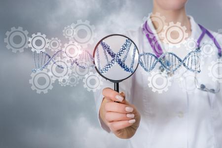 Un primer plano de un médico que muestra el mecanismo genético del modelo de adn y los engranajes colocados a través de la lupa. El concepto de herencia genética.