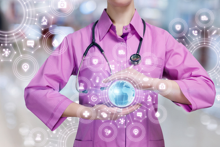 A closeup of a doctor with a stethoscope holding a globe inside a total medical service structure scheme at blurred background. The concept of global entire medical service structure.