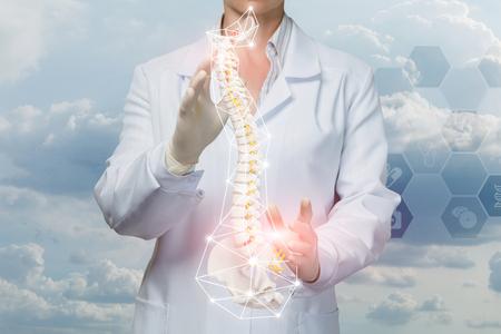 Lekarz operuje ze sztucznym kręgosłupem z miednicą zjednoczoną wewnątrz klatki cyfrowych połączeń bezprzewodowych na tle grzebienia systemu usług medycznych. Koncepcja leczenia schorzeń kręgosłupa.