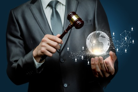A closeup of a man holding a hammer and a globe with social network system with human figures icons at dark background. The concept of international auction.