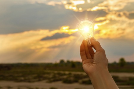 Light Bulb above sunset in hand. The concept of innovative ideas.