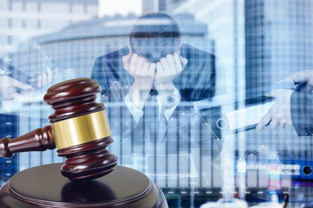 The concept of bankruptcy of the business. A closeup of an auction gavel with a transparent figure of stressed businessman in despair at the blurred business center background.