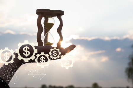 Innovatief mechanisme van financiële ontwikkeling. Een close-up van een vrouwelijke hand met zandhorloge met het tandradmechanisme van het geldsysteem met valuta-eenheden erin.