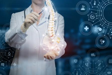 Le docteur montre une colonne vertébrale humaine sur fond bleu.
