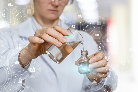 A lab worker mixes substances on a blurred background.