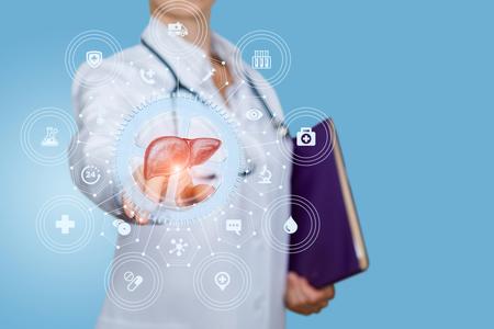 Un operatore medico esegue un test del fegato su sfondo blu. Archivio Fotografico