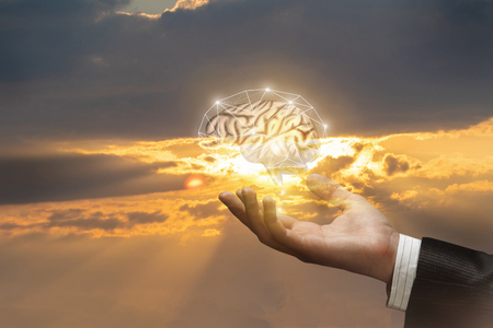 The hand of a businessman supports the brain against the sky. Concept of brainstorming and ideas in business.