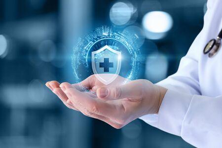 Der Arzt zeigt das Symbol des Gesundheitsschutzes auf unscharfem Hintergrund. Standard-Bild