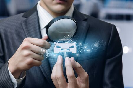 The concept of inspection and examination of the car . Businessman looking at a car through a magnifying glass. Banco de Imagens