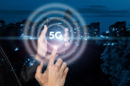 5G Wireless System concept. The businessman clicks the phone on the background of the city.