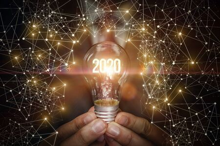 The concept of a new year with new ideas. Hand showing light bulb with luminous numbers 2020.