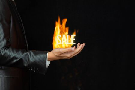 The concept of burning best offer in the business. Businessman showing a burning inscription sale.