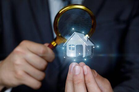 Le concept de l'étude et de l'inspection des biens immobiliers. L'agent regarde la maison modèle à travers une loupe. Banque d'images