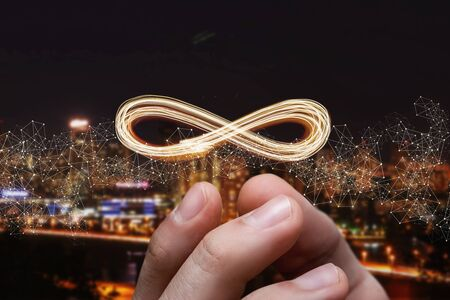 Unlimited internet concept. Hand shows sign of infinity on the background of the city.