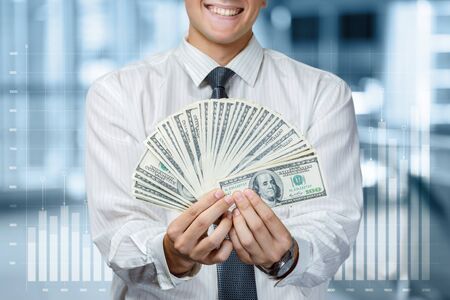 The concept of profit and financial success in business. Businessman showing dollars on blurred background. Stock Photo