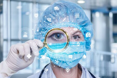The concept of examination of the patient. The doctor looks through a magnifying glass on a blurred background. Banco de Imagens