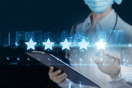 The concept rating of medical care. The doctor clicks a star on the blurred background of the city.
