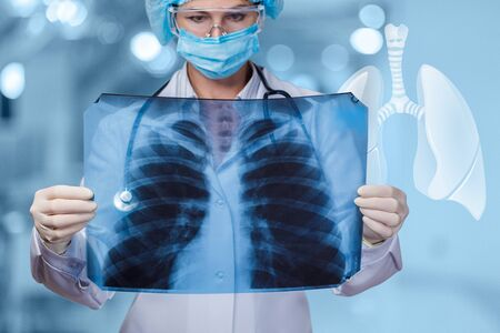The doctor examines the patients lungs on blurred background. Doctor looking at an x-ray of the lungs .