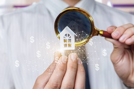 The agent evaluates a property . Man looks through a magnifying glass at a model home.