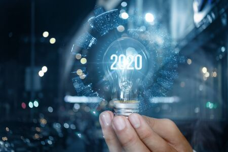 The concept of a new business in 2020 . Businessman with a bulb burning in the hand.