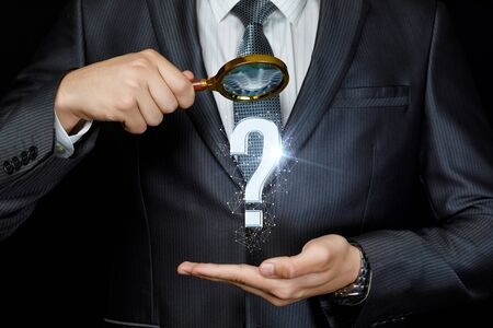 The concept of the search for the answer to the question. Businessman looking through a magnifying glass to a question mark.