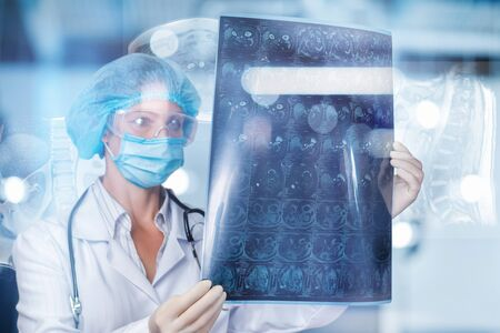 A doctor is examining a magnetic resonance imaging scan on a blurred background.