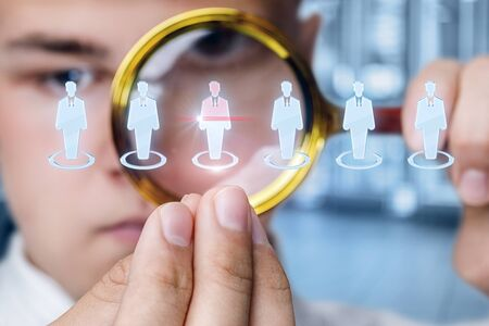The concept of the choice of the employee . Businessman studies candidates with a magnifying glass.