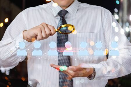 The choice of the employee . Businessman studies candidates with a magnifying glass. Stock Photo