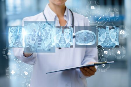 Doctor examines of magnetic resonance imaging on blurred background .