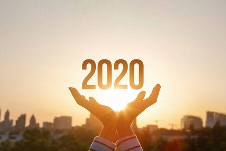 El concepto nuevo año 2020. Las manos muestran 2020 en el fondo del atardecer. Foto de archivo