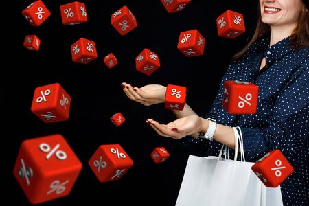 The concept of discounts on black Friday. Shopper catches the cubes with interest on a black background.